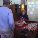 Gram's giftwrapping present for veteran at toy giveaway